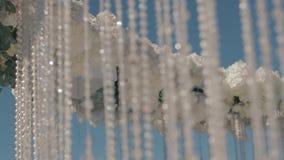 Алтар свадьбы Цепи Кристл висят от алтара свадьбы с белыми розами пока он стоит на береге озера снаружи сток-видео