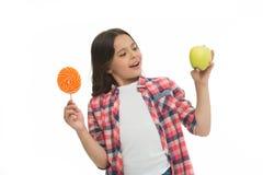 алтернатива здоровая Смогите засахарить сладостный вкус сделайте нас счастливый Девушка держит сладкие леденец на палочке и яблок стоковое фото