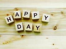 Алфавит блока счастливого дня деревянный на деревянной предпосылке Стоковые Фото