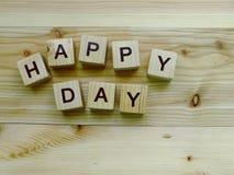 Алфавит блока счастливого дня деревянный на деревянной предпосылке Стоковые Фотографии RF