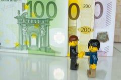 Алькобендас, Испания - 14-ое мая 2018: Рукопожатие для согласования на предпосылке счетов, minifigures Lego изготовлено Lego стоковая фотография
