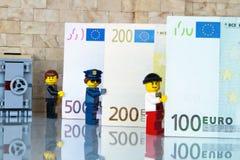 Алькобендас, Испания - 14-ое мая 2018: Minifigures LEGO держа предпосылку счетов, minifigures Lego изготовлены группой Lego стоковое фото rf