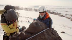 Альпинисты подготавливают спустить на веревочку, они связывают веревочку к камню и регулируют оборудование На заднем плане, a видеоматериал