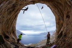 Альпинисты утеса в пещере: belayers наблюдая ведущие альпинистов Стоковое Фото