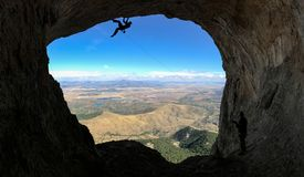 Альпинист в высоких горах на выходе пещеры Стоковое Изображение RF