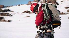 Альпинист в красном обмундировании, с рюкзаком со шлемом и изумленными взглядами Он выправляет и обеспечивает веревочку к его видеоматериал
