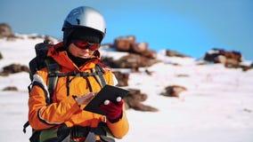 Альпинист в особенном обмундировании стоит на покрытом снег наклоне и проверяет маршрут на карте на вашем планшете сток-видео