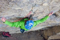 Альпинист девушки на утесе Стоковая Фотография