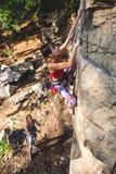 Альпинист девушки на утесе Стоковые Изображения