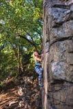 Альпинист девушки на утесе Стоковое Фото