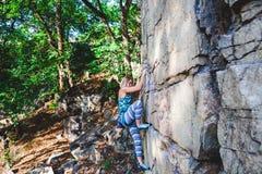 Альпинист девушки на утесе Стоковое Изображение RF