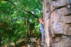 Альпинист девушки на утесе Стоковая Фотография RF