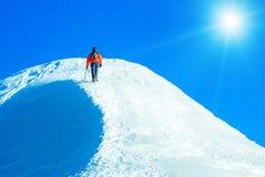 Альпинист достигает саммит горного пика Взбираться и mounta Стоковая Фотография RF