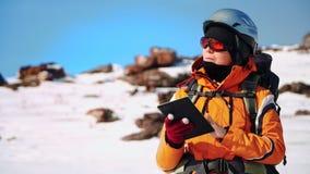 Альпинист нося шлем, солнечные очки и планшет в его стойках руки на снежном холме Исследования карта и взгляды акции видеоматериалы