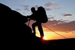 альпинист предпосылки идет заход солнца s гористый Стоковое фото RF