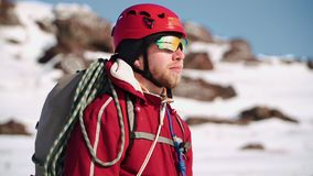 Альпинист с бородой нося шлем и особенные стекла стоя на горнолыжном склоне, смотрит вокруг и наслаждается взглядом сток-видео