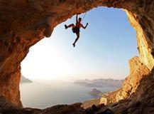 Альпинист утеса на заходе солнца Стоковые Изображения RF