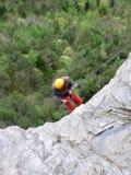 Альпинист утеса rappeling от серой скалы утеса в сочный зеленый лес ниже стоковая фотография