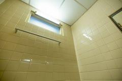 Алюминиевая вешалка полотенца на квадратной плитке стены в ванной комнате стоковое фото