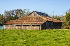 Амбар старой склонности деревянный с заржаветой крышей олова Стоковое фото RF