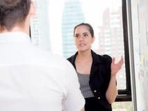 Американская бизнес-леди в современном офисе смотря отчет и анализировать Стоковая Фотография RF
