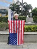 Американская выставка человека американский флаг с КОЗЫРЕМ ` слов НАША ТРАГЕДИЯ ` На беспроволочной дороге около посольства США в Стоковое Изображение RF