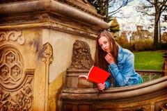 Американская книга чтения девочка-подростка снаружи на кампусе в Нью-Йорке Стоковая Фотография RF
