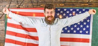 Американская концепция системы образования Человек с бородой и усиком на счастливой стороне держит флаг США, деревянную предпосыл стоковое фото