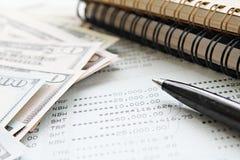 Американские деньги наличных денег доллара, бумага тетради, ручка и банковская книжка на предъявителя или финансовый отчет сберег Стоковое фото RF