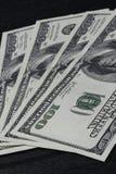 американские доллары в черной предпосылке Стоковые Изображения
