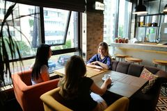 Американские женщины сидя на уютном кофе кафа, усмехаться и выпивать Стоковая Фотография