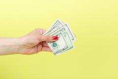 Американские доллары в руке ` s женщины, желтой предпосылке Стоковое фото RF