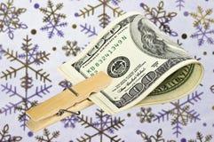 Американские доллары с зажимкой для белья на предпосылке snowflak Стоковое Фото