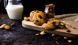 Американские печенья shortbread с падениями шоколада и кувшин молока и миндалин Темная предпосылка grunge Мистический свет стоковые фото