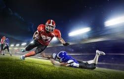 Американские футболисты в действии на грандиозной арене стоковые фотографии rf