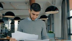 Американский бизнесмен смотря проект запуска, работая на таблице в современном кафе сток-видео