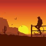 Американский ковбой на ландшафте захода солнца Диких Западов в вечере Стоковые Изображения RF