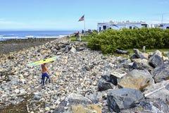 Американский ландшафт при серфер идя вверх с его surfboard к располагаясь лагерем тележке на длинном пляже песка, Мейне, США стоковые фотографии rf