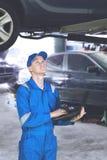 Американский механик стоя под поднятым автомобилем Стоковые Изображения