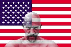Американский патриот смотря вас с флагом США на заднем плане Стоковое Изображение RF