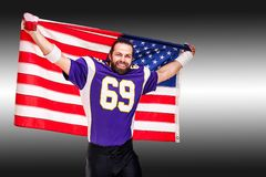 Американский портрет крупного плана футболиста Американский футболист с американским флагом в его руках r стоковое фото rf