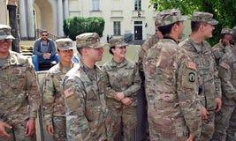 Американский солдат в равномерном и гражданском человеке в костюме тряся руки стоковое фото rf