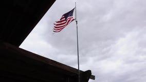 Американский флаг летает под clody небо на ветреный день Флаг был старым и трепал видеоматериал