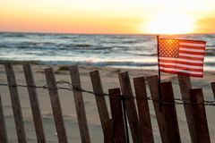 Американский флаг на загородке пляжа с заревом захода солнца Стоковое Изображение RF