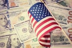 Американский флаг на предпосылке счетов доллара США принципиальная схема финансовохозяйственная r Стоковое Фото