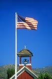 Американский флаг развевая над одним зданием школы комнаты, Стоковые Изображения RF