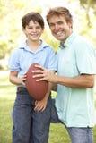 американский футбол отца играя сынка совместно Стоковая Фотография