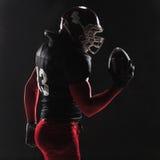 Американский футболист представляя с шариком на черной предпосылке стоковая фотография rf