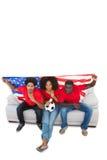 Американский футбол дует в красном цвете на софе Стоковая Фотография RF