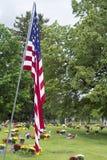 Американский флаг и цветки на Graveside ветерана стоковые изображения
